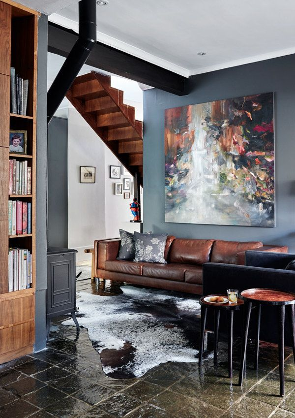 In the living area, the inviting leather couch is a Klooftique (klooftique.com) design; the Nguni-skin rug is also from Klooftique. The painting – which provides a gorgeous pop of colour on the chic grey wall – is by Cathy Layzell (cathylayzell.com).