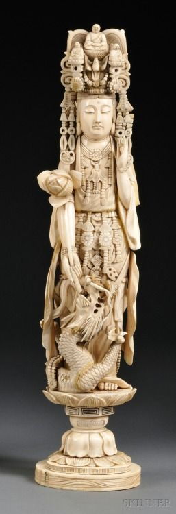 """ Kwan Yin, China, 19th century, in adorned clothing and headdress, left hand in the mudra of appeasement position, right hand holding a lotus blossom, a swirling dragon at feet, standing on a lotus base. """