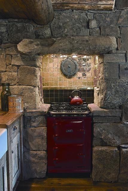 Stone kitchen with red stove at Cutthroat Cabin | Custom Montana & Wyoming Homes | On Site Management | OSM - #WesternHome