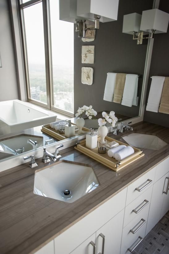 For cohesiveness, interior designer Lindsay Pumpa chose two hexagon-shaped sinks to echo custom-cut crystals displayed in the ceiling light fixture. A marble countertop mimics the mink-colored walls of this dramatic master bath. #HGTVUrbanOasis