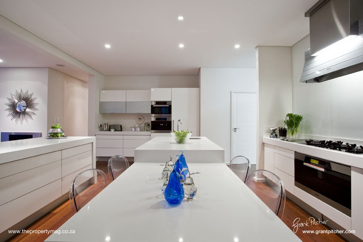 Modern Kitchen, wooden floors, white granite counter tops, white doors and cabinets, down lights