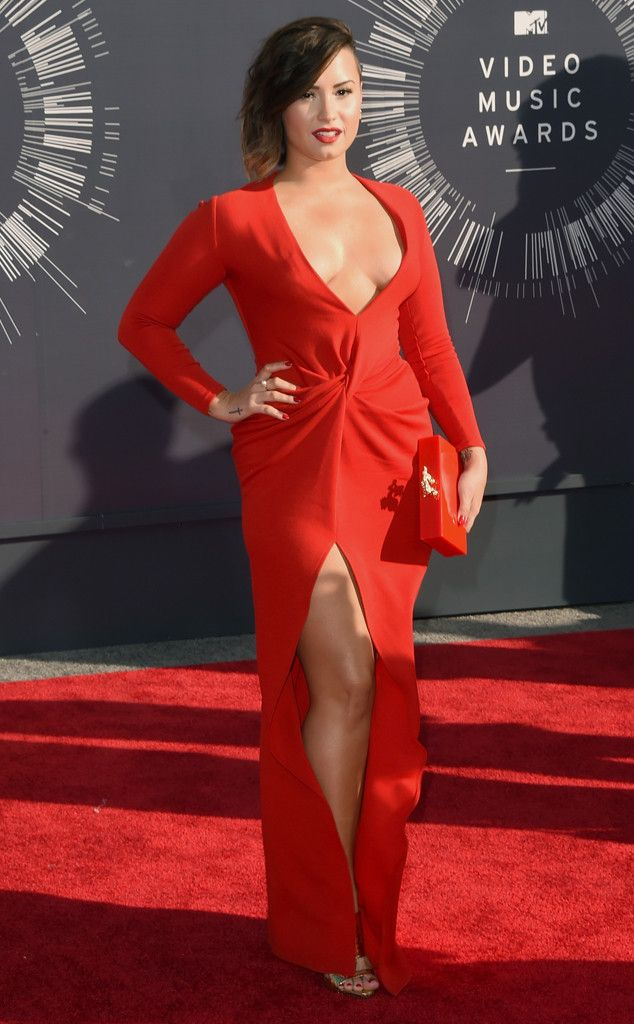 Demi Lovato flaunts tons of cleavage in a flaming red dress with matching lipstick and nail polish.