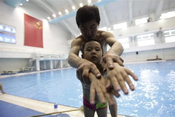 A coach helps a boy learn swimming posture before a diving training session at a training center in Beijing, July 27, 2011.  REUTERS/Jason Lee