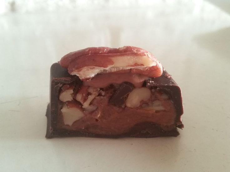 pure chocolade bonbons met een vulling van nougatcrème en pecannoten