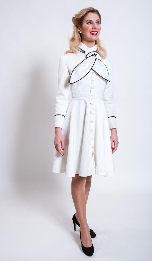 Vestido abrigo en cloque color blanco roto con vivos negros. Lazada sobre el cuello, manga larga, falda de capa. Cinturón forrado. https://www.facebook.com/media/set/?set=a.766776350016058.1073741834.565541916806170&type=3