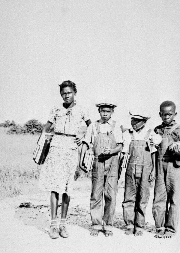 children on their way to school - Dade County, Florida, 1937. The boys are sure scowling at the photographer - wonder who was taking the picture? They are barefoot, and their overalls were bought long so they could grow into them - may be early in the school year. The older girl has shoes and very stylish socks