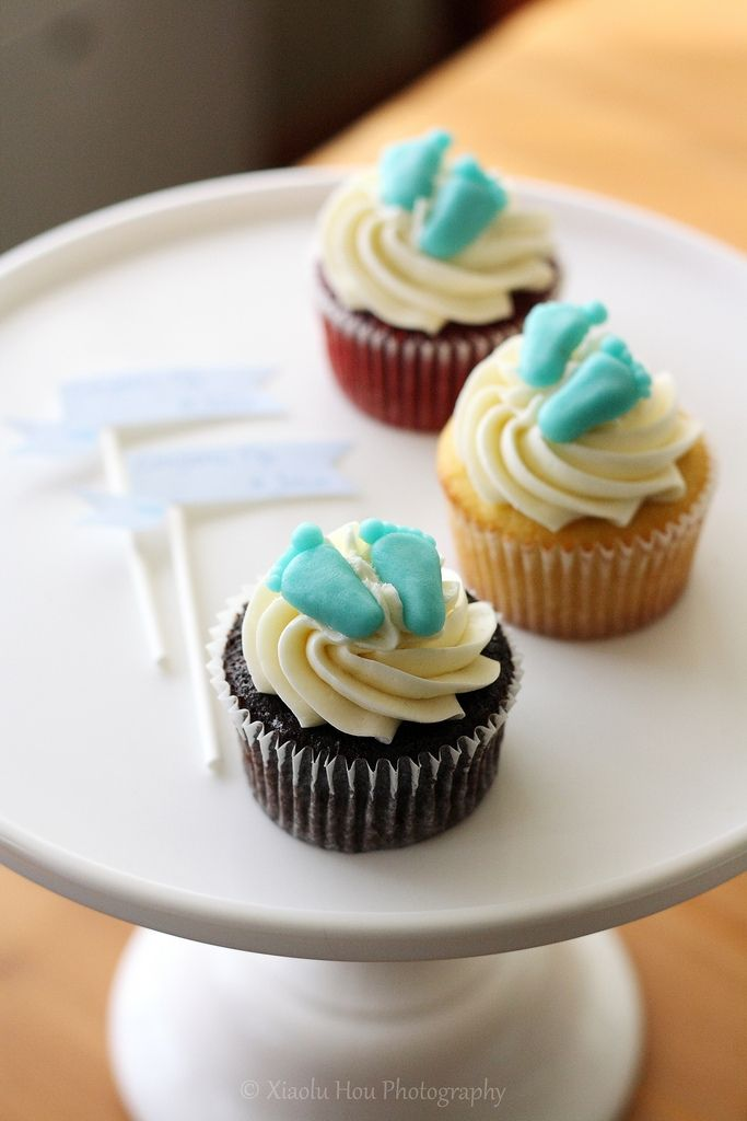 Baby Shower Cupcakes - Red velvet, vanilla, and chocolate cupcakes for a baby shower. Small baby footprints made from marzipan dyed blue (baby is male).