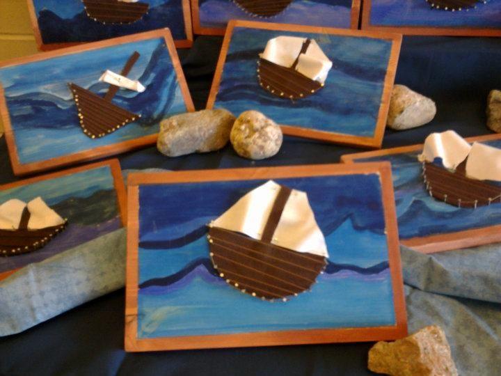 """""""Purjelaivoja"""" (2.lk). Ensin puulevy hiotaan tasaiseksi, sitten teipit reunoihin ja maalaaminen paksuilla peiteväreillä (kolmella eri sinisellä). Teipit pois ja kehysten maalaaminen ruskealla. Sitten leikataan huovasta laiva ja masto. Naulataan laivan reunoille pienet naulat, joiden avulla pujotellaan lanka. Lopuksi leikataan lakanakankaasta purjeet, jotka naulataan """"pullottamaan tuulessa"""". (Alkuopettajat FB -sivustosta / Eeva Pauliina)"""
