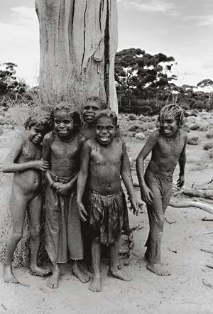 This sweet photograph by Alastair McNaughton is of Aboriginal children after they've been playing in the mud - a black and white picturecard, a little larger than the average postcard.