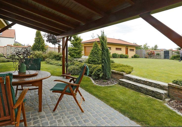Pohled z terasy domu do velkorysé zahrady s velkou travnatou plochou.