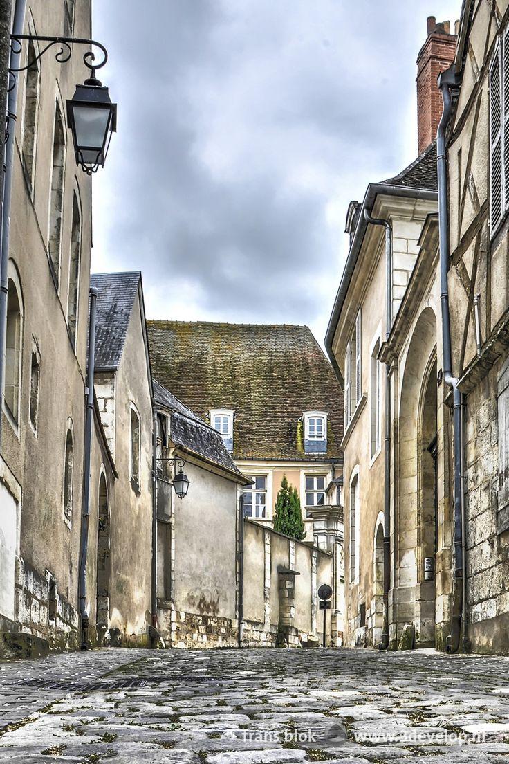 Kasseien, een lantaarn, een vakwerkgevel, een poort en andere historische elementen in een bocht van de rue de l'hotel de l'allemant in het middeleeuwse centrum van Bourges, midden-Frankrijk. - Cobblestones, a lantern, a half-timbered facade, a gate and other historic elements in a bend of the rue de l'hotel de l'Allemant in the medieval center of Bourges, central France. -