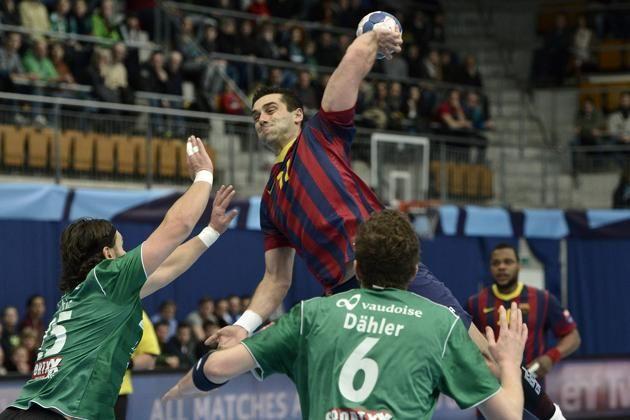 Wacker Thun's Nikola Dokic, left, and Jonas Daehler, right, try to stop Barcelona's Kiril Lazarov, center, during the EHF Champions ...