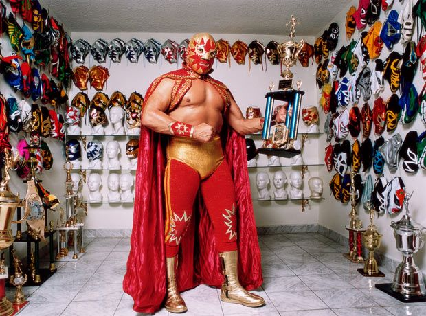 Solar holds a trophy in a room lined with Mexican wrestling masks