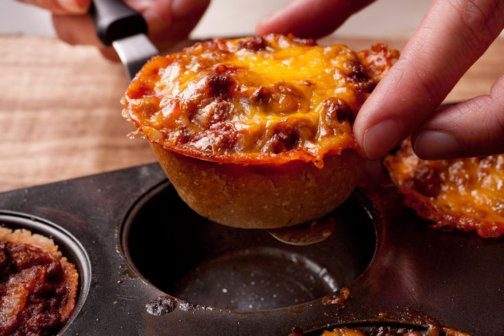 This mini tamale pie recipe has a savory ground beef filling tucked into a crispy masa shell and topped with sour cream and cilantro. #Tamale #MiniPies #MuffinPan