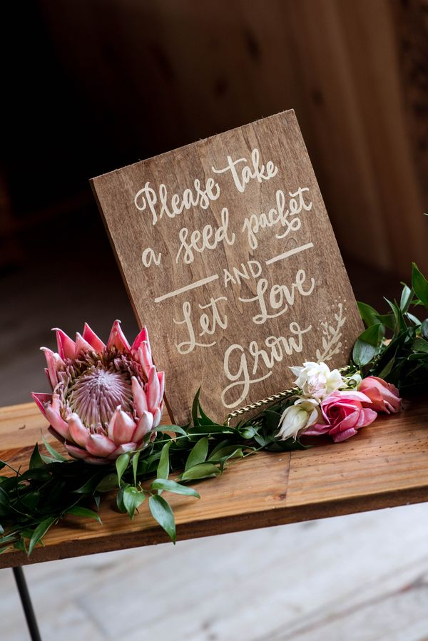 Wooden wedding sign for seed wedding favors, with king protea accent. Bohemian Romance Meets Barn Wood Inspiration