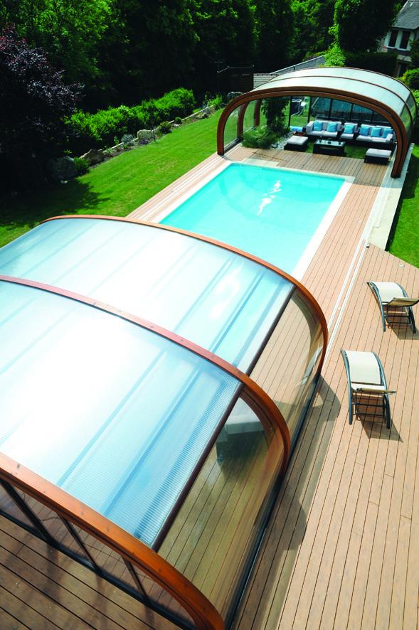 Esta cubierta telescópica, realizada con arcos de madera laminada, crea un espacio de ocio polivalente junto a la piscina