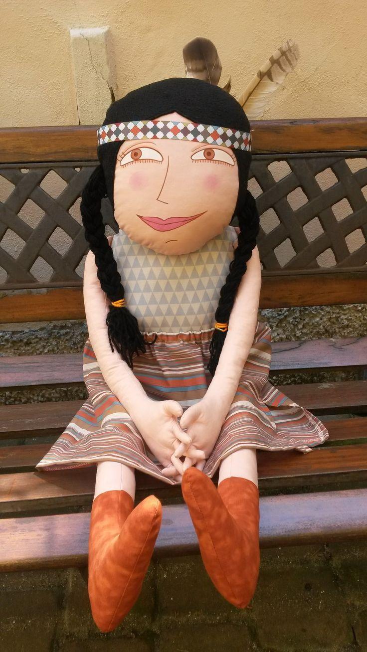 """Krásný den je jméno téhle indiánské holky. Hodně velká (cca 85 cm) """"hadrová"""" panenka je ušitá z bavlněných látek, vlasy má z fleece a copy z vlny, výplň pes kuličky. Obličej je namalovaný štětcem nezávadnými textilními barvami fixovanými zažehlením. Ručičky má s pěti prsty. Sukně je svlíkací, čelenka je sundavací, pera jsou pouze zastrčená. Poslední fotka s ..."""