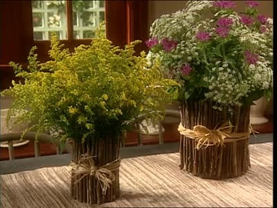 Martha Stewart creates a beautiful twig vase out of a coffee can, half a plastic water bottle and a bunch of twigs.