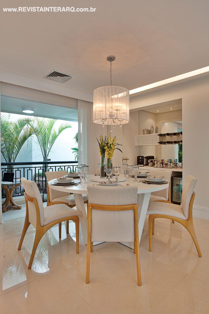 A cozinha com móveis planejados amadeirados conta com uma extensa bancada em Silestone branco com espaço para lanches rápidos. O quadro de vidro funciona como lousa para recados.