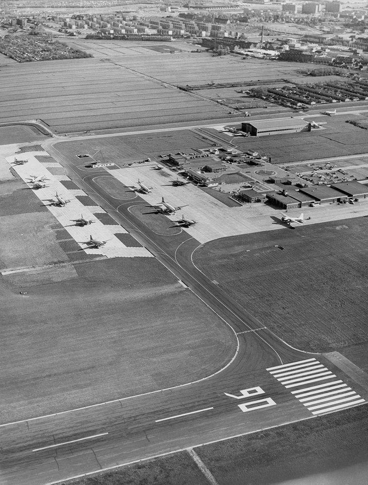 Rotterdam - Vliegveld 'Zestienhoven'. Deze luchtfoto werd 5 jaar na de opening van de luchthaven gemaakt. Er is een extra stuk platform bijgebouwd en er is een hangaar bijgekomen.