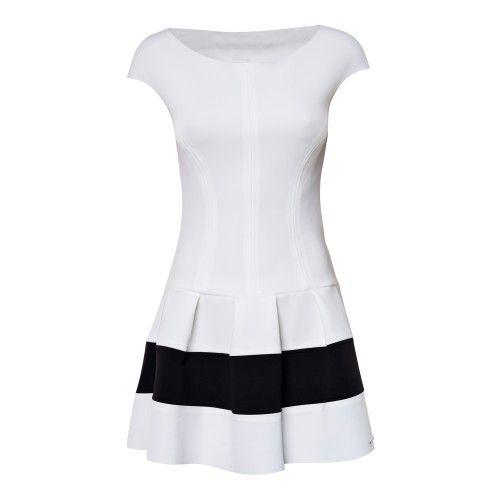 Korte witte jurk in rekstof met kapmouwtjes. Bovenstuk sluit aan, onderaan klokrokje met zwarte band. Op de rug zwart kanten inzetstuk. De pop draagt S.