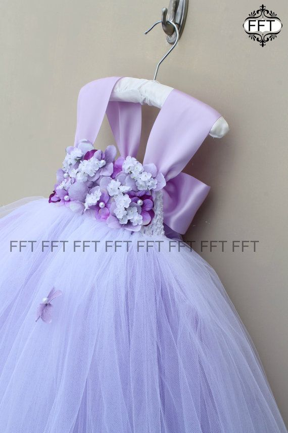 This dress is a lovely mix of lavenders and is so pretty in person! The flower mix consists of 2 shades of lavender hydrangea, a hint of royal purple for added depth / visual interest (royal purple can be eliminated upon request) and off white flowers. Pearls are added in the centers of some flowers for added elegance. The skirt portion is lavender with a white overlay so the lavender can softly filter through. Flowers are also added to the skirt portion but can be eliminated upon reques...