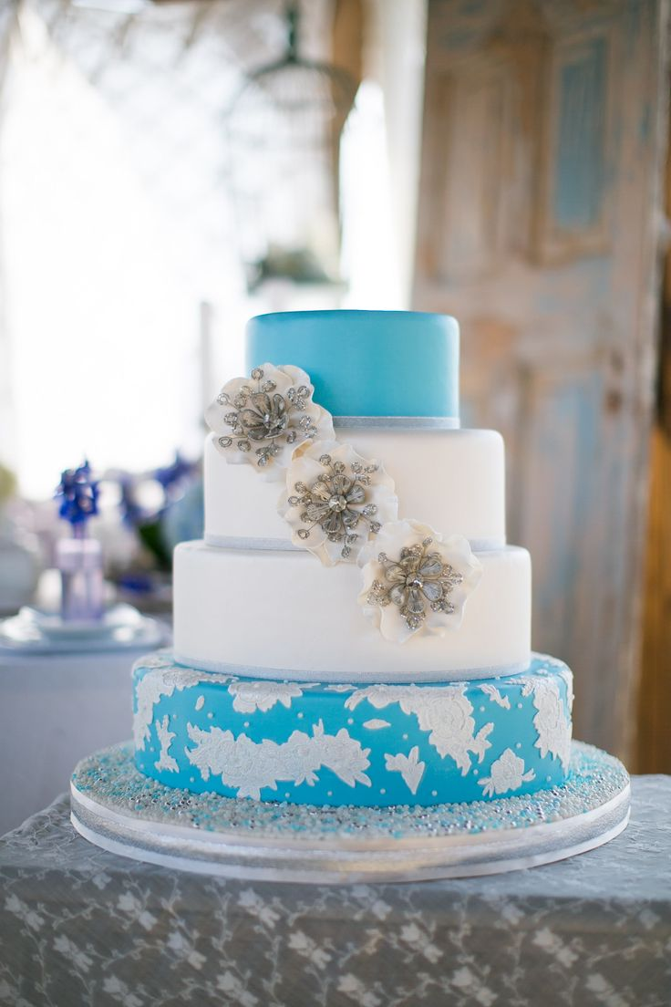 Ocean blue and white oval wedding cake with lace appliques.