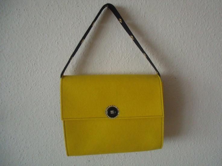 Ausgefallene gelb-schwarze Filztasche mit Klappe, Klettverschluss. Verziert mit einem strassgeschmückten Knopf. Der Schulterriemen  ist mit goldfb. Ös