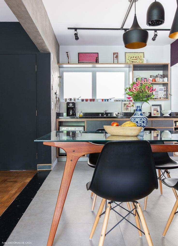 Cozinha integrada à sala tem mesa vintage e cadeiras Eames.