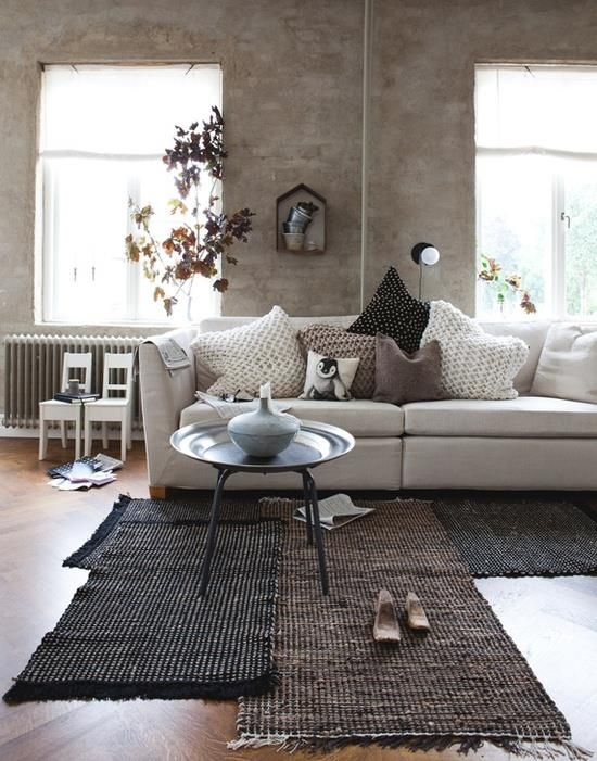 Interesting rug layout for a shabby-chic effect. Welcoming and comfortable in passive neutrals.
