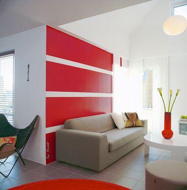 Une déco contemporaine avec une utilisation de la peinture salon originale. Sur la pan de mur du canapé gris des bandes de peinture rouge et blanche à l'horizontale. Pour faire un rappel de couleur, un tapis rouge et une autre touche avec le vase sur la table basse