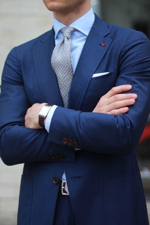 Den Look kaufen: https://lookastic.de/herrenmode/wie-kombinieren/anzug-businesshemd-krawatte/17089   — Hellblaues Businesshemd  — Roter Anstecknadel  — Graue gepunktete Krawatte  — Weißes Einstecktuch  — Dunkelbraune Lederuhr  — Dunkelblauer Anzug  — Dunkelbrauner Ledergürtel