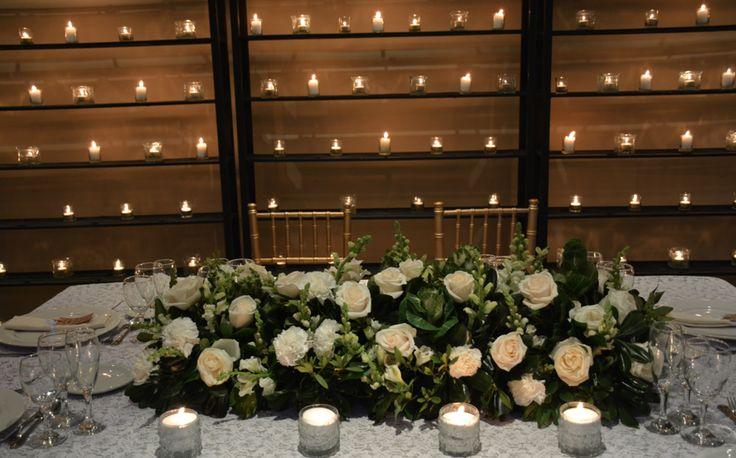 Mesa principal para dos, los novios: cantero de flores blancas, follaje, y repollos verdes.  Fondo de estanterias con filas de mini velas y sillas tiffany doradas. by Mercedes Courreges Ambientaciones