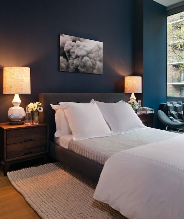 Blue bedroom with peacock blue walls paint color, charcoal gray modern platform bed, crisp white duvet & shams, natural woven rug, contemporary coffee stained wood nightstands and West Elm Terracotta Lamps.