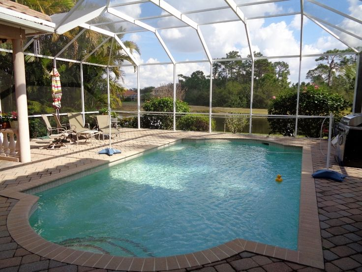 swimming pool in Bradenton home with brick pavers overlooking lake