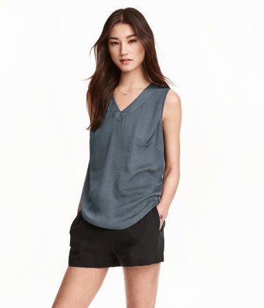 Sleeveless V-neck blouse in airy woven fabric with a sheen. Rounded hem.