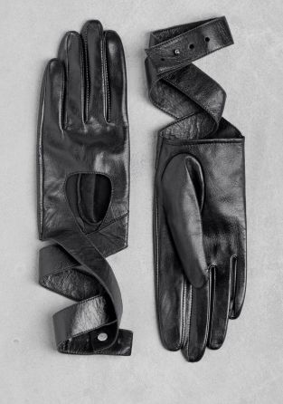Made from smooth, buttery leather, these short gloves have a wrap-around design. - Cut-out section in the front- Leather straps that wrap around the wrist (adjustable length)- Metal cufflink button to close- Soft fabric lining