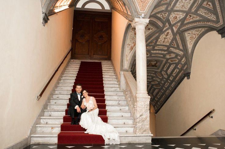 Gli sposi innamorati seduti sulla alte scalinate del palazzo.