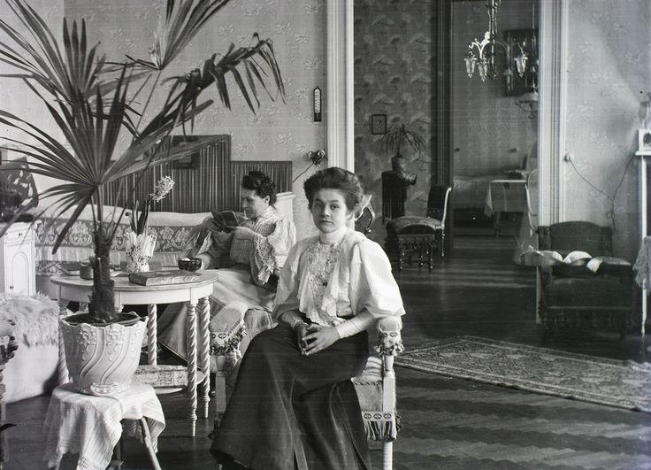 A tágas otthonokat a legkorszerűbb felszerelésekkel látták el: az ajtó mellett ott látható például a telefonzsinór. Érdemes megfigyelni, mennyire kevesett változott a növénydivat: a legyezőpálma, vagy az asztalon becsomagolt jácint akár egy mai lakásban is lehetne. Igaz, egy évszázaddal ezelőtt talán még ez is a luxus része volt.