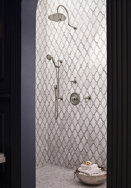 Mediterranean style bathroom features walk-in shower adorned with gray arabesque tile surround over marble hex shower floor along with dual shower heads.