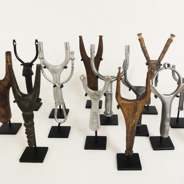 """A collection of 15 antique and vintage slingshots dating from the turn of the century to the 1950's. Wood and metal. Homemade and manufactured. Each slingshot mounted on its own custom made steel stand and displayed in a custom made black painted maple shadow box measuring 25"""" x 33"""" x 2""""."""
