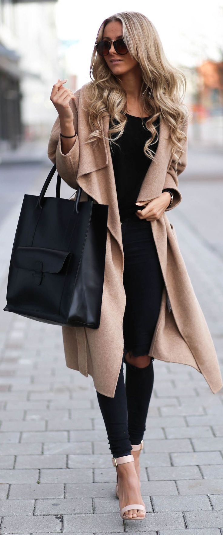 Shop this look on Lookastic:  http://lookastic.com/women/looks/sunglasses-coat-tank-tote-bag-skinny-jeans-heeled-sandals/6095  — Dark Brown Sunglasses  — Camel Coat  — Black Tank  — Black Leather Tote Bag  — Black Ripped Skinny Jeans  — Beige Leather Heeled Sandals