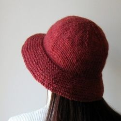 The knitted hat was hand-knitted with acrylic wool blend yarn. It has a cup and a wide and downwards sloping brim.