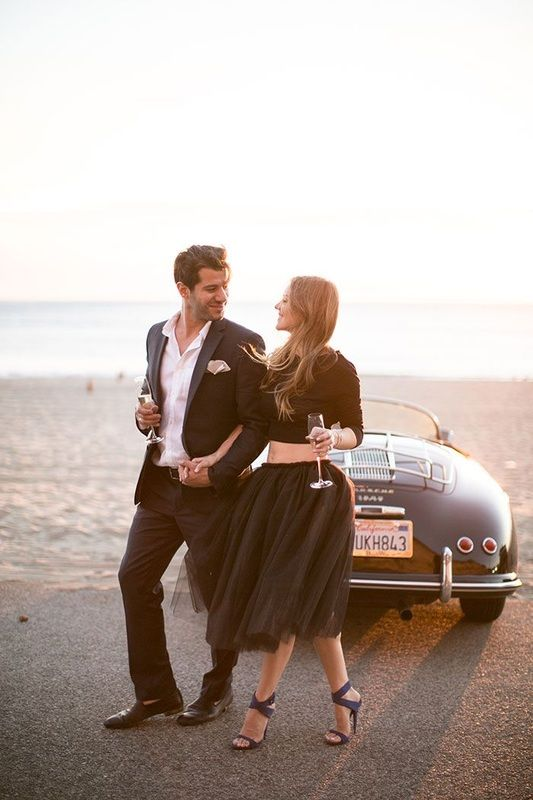 fiances walking next to vintage car on the beach wearing a suit and girl in a black tulle skirt http://www.itgirlweddings.com/blog/stylish-engagement-shoot