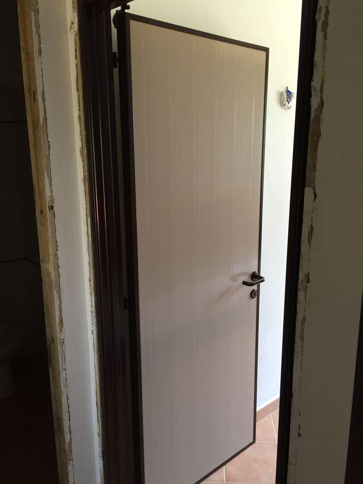 Fase di montaggio di una Porta interna in Pvc, con pannello liscio beige, cornicetta, telaio, coprifili e maniglia marrone.