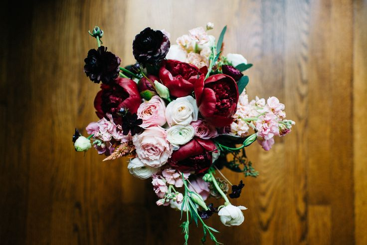 Rich tones of burgundy offset by blushes and whites make up this beautiful bridal bouquet of red charm peonies, burgundy ranunculus, Kiera garden rose, white ranunculus, peach stock, white lisianthus, white majolica spray rose, peach celosia, chocolate cosmos, scabiosa pods, seeded eucalyptus.