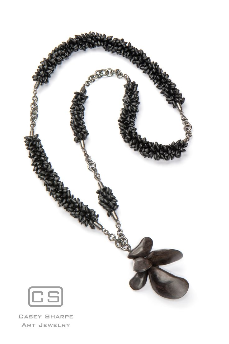 """Salt and Brine -    Each mussel was carved from a block of African Blackwood before being sanded to a fine finish and coated with the thinnest layer of wax to add shine. The necklace also features glass beads in kumihimo braiding, alternating with handmade sterling silver caps and graduated sections of sterling silver chain.  Measures 19"""" x 2"""" x 1.25"""""""