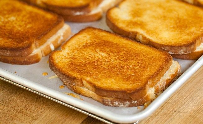 Make 8 grilled cheeses at once! Bake them between two baking sheets.