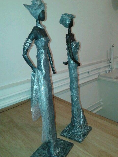 Beelden Afrikaanse vrouwen.  Gemaakt van klei en gips en afgewerkt met paverpol.  Zwart en zilverkleurig. 65 en 70 cm