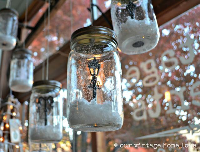 "LOVE these ""snow globes.""  Fake snow lightly sprayed in them, miniature street lamps put inside, hung from an old ladder at varying heights like lanterns.  SO cute!  (from our vintage home love)"